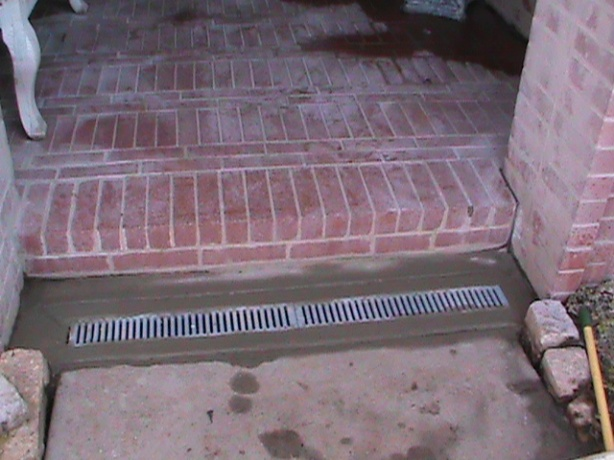 Channel Drain installed in a sidewalk by a front door.