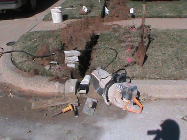 Installing French Drain and Curb Outlet  in Drainage System in Norman.