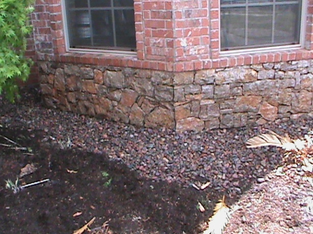 French Drain with colored river rock along foundation