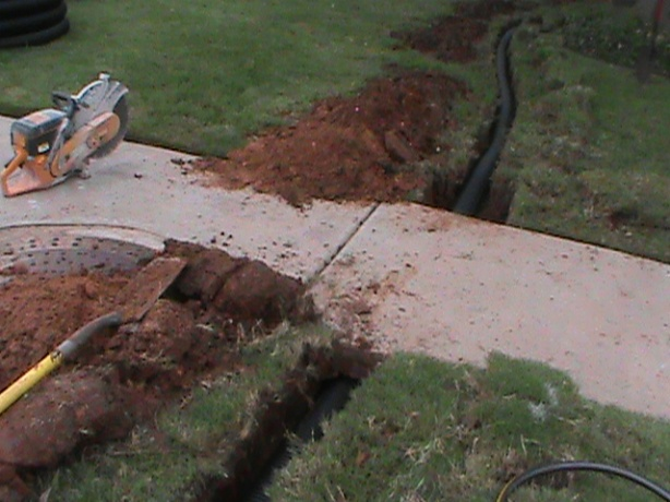 Installing Drain Pipe under Sidewalk From French Drain in Back