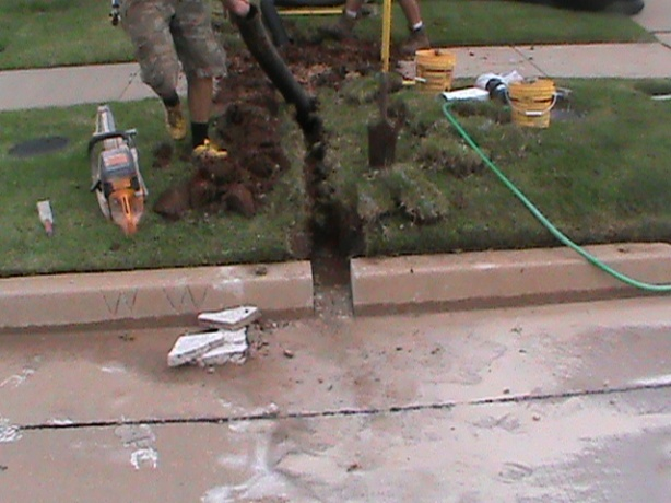 Installing Curb Outlet for French Drain in Norman