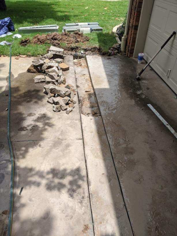 cutting the driveway for a channel drain